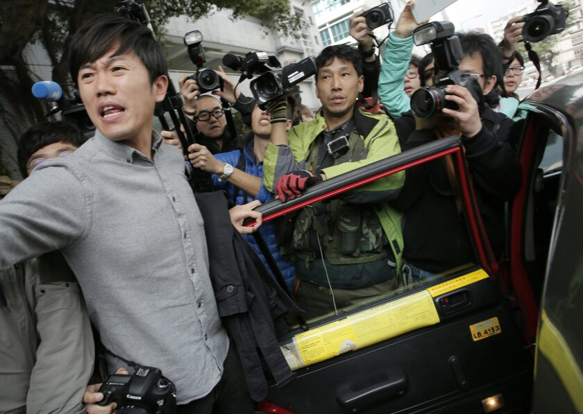 A supporter tries to make way for a suspect to get in a taxi as he leaves a court after on bail in Hong Kong, Thursday, Feb. 11, 2016. Several dozen people appeared in a Hong Kong court Thursday to face rioting charges following a violent clash earlier this week between protesters and police sparke