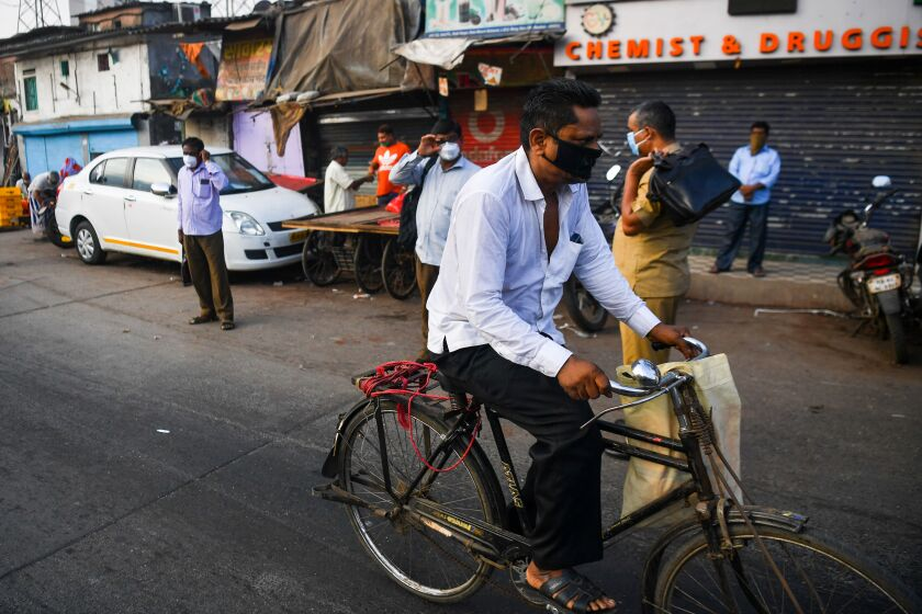 A cyclist rides past a bus stop outside the Dharavi slum in Mumbai, India, during the nationwide lockdown to combat the coronavirus.