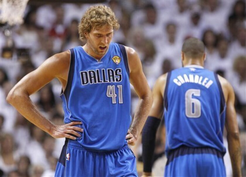 Dallas Mavericks' Dirk Nowitzki (41) takes a break as Tyson Chandler (6) is seen on right, during the first half of Game 1 of the NBA Finals basketball game against the Miami Heat, Tuesday, May 31, 2011, in Miami. (AP Photo/Lynne Sladky)