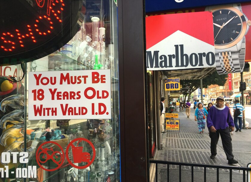 """A sign posted outdoors at a smoke shop reads """"You Must Be 18 Years Old with Valid I.D.,"""" in downtown Los Angeles on Wednesday, June 8, 2016. Smokers have to be 21 and older to buy tobacco products in California under a new law that takes effect on Thursday. California is the second state after Hawa"""