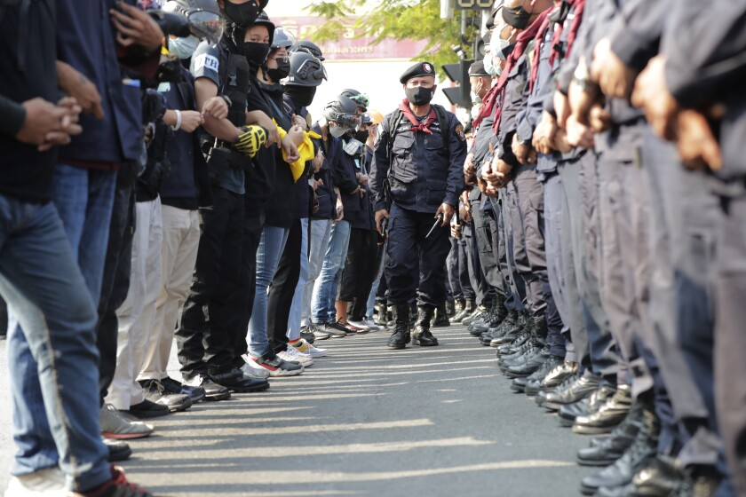 A Thai policeman walks between protesters and police lines facing each other during a pro-democracy rally Thursday, Dec. 10, 2020 in Bangkok, Thailand. Despite legal charges being filed against the leaders, pro-democracy demonstrators continue their protests calling for the government to step down and reforms to the constitution and the monarchy. (AP Photo/Gemunu Amarasinghe)