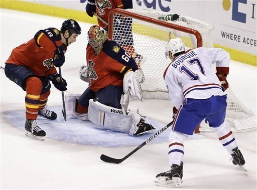 Montreal Canadiens left wing Rene Bourque (17) scores a goal against Florida Panthers goalie Jose Theodore (60) and center Shawn Matthias (18) during overtime in an NHL hockey game, Thursday, Feb. 14, 2013 in Sunrise, Fla. The Canadiens won 1-0. (AP Photo/Wilfredo Lee)