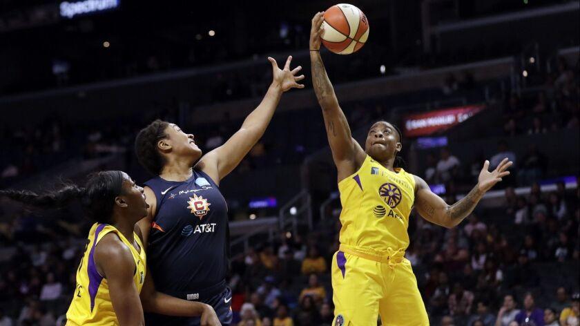 Los Angeles Sparks' Riquna Williams, right, grabs a rebound next to Connecticut Sun's Morgan Tuck, c