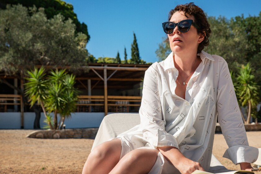 Olivia Colman, wearing sunglasses, sits on a beach chair and looks out.
