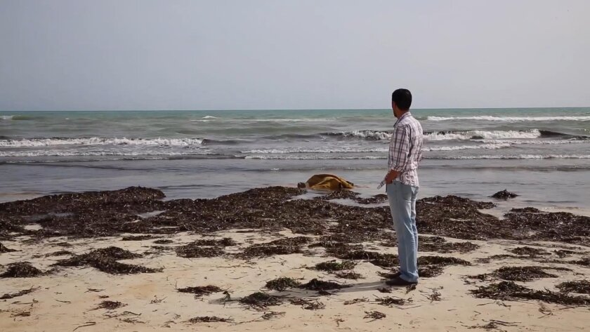 A local Zwara resident views the body of a victim, laying in the surf at centre, as more than 100 bodies are pulled from the sea near the western city of Zwara, Libya, Friday June 3, 2016, after a smuggling boat carrying mainly African migrants sank into the Mediterranean.  Libya's navy spokesman C