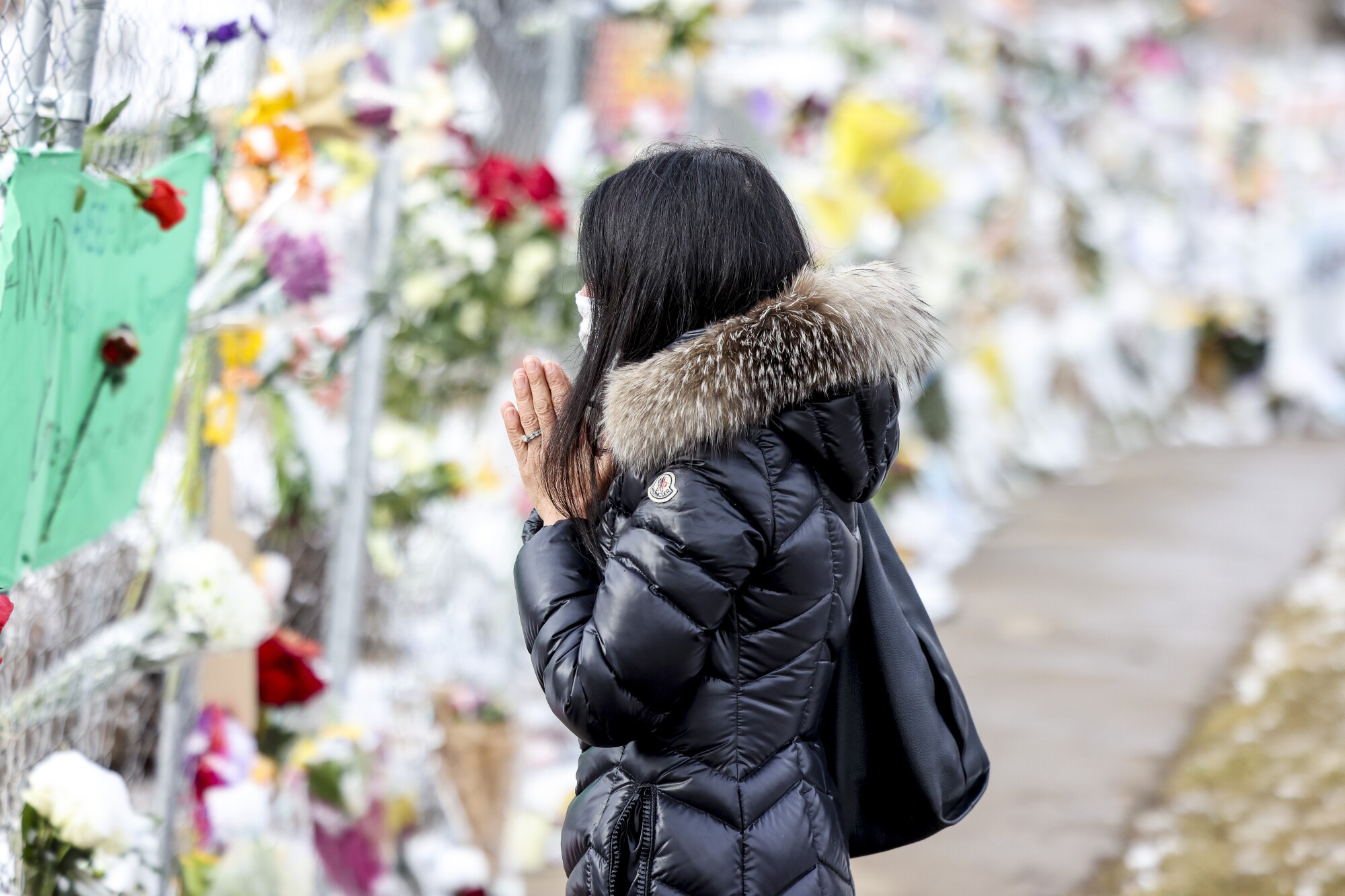 A woman stands with her hands clasped in front of a display of flowers on a sidewalk
