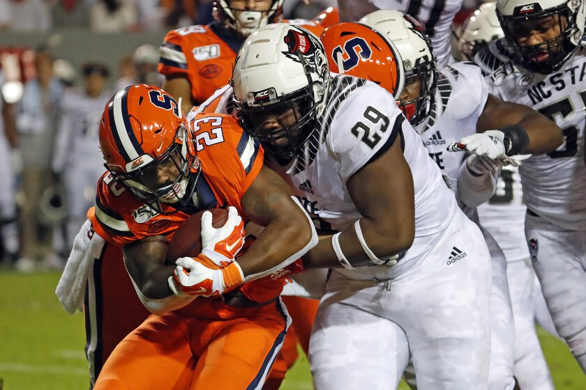 North Carolina State's Alim McNeill (29) ties up Syracuse's Abdul Adams (23) during the first half of an NCAA college football game in Raleigh, N.C., Thursday, Oct. 10, 2019. (AP Photo/Karl B DeBlaker)