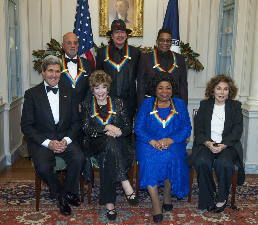 Secretary of State John Kerry, with the 2013 Kennedy Center honorees, from left, seated Shirley MacLain, and Martina Arroyo, along with Teresa Heinz Kerry. Standing are Billy Joel, Carlos Santana, and Herbie Hancock, pose for a photo at the State Department for the Kennedy Center Honors gala dinner on Saturday, Dec. 7, 2013 in Washington. (AP Photo/Kevin Wolf)