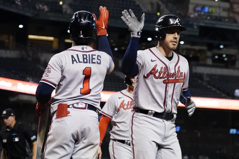 El jugador de los Bravos de Atlanta Freddie Freeman choca con Ozzie Albies (1) tras pegar un jonrón de dos carreras en el noveno inning de su juego de béisbol el miércoles 22 de septiembre de 2021 en Phoenix. (AP Foto/Matt York)