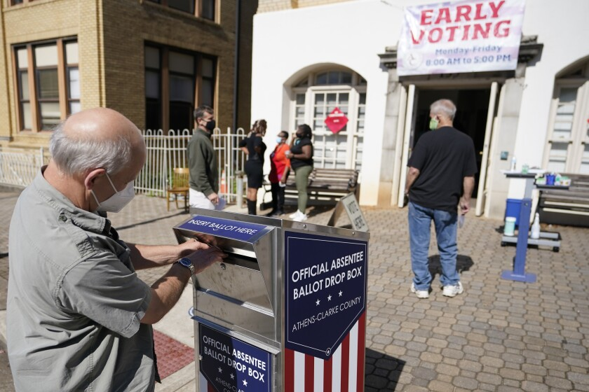 """FILE - In this Monday, Oct. 19, 2020 file photo, a voter submits a ballot in an official drop box during early voting in Athens, Ga. On Friday, April 2, 2021, The Associated Press reported on stories circulating online incorrectly asserting """"Georgia's new anti-voting law makes it a jail-time crime to drop off grandma's absentee ballot in a drop box."""" But the election bill known as SB 202, signed into law on March 25, has an exception allowing people to drop off ballots on behalf of their relatives. It also allows a caregiver to deliver a completed ballot on behalf of a disabled person, or a jail employee to deliver a completed ballot on behalf of someone who is in custody. (AP Photo/John Bazemore)"""