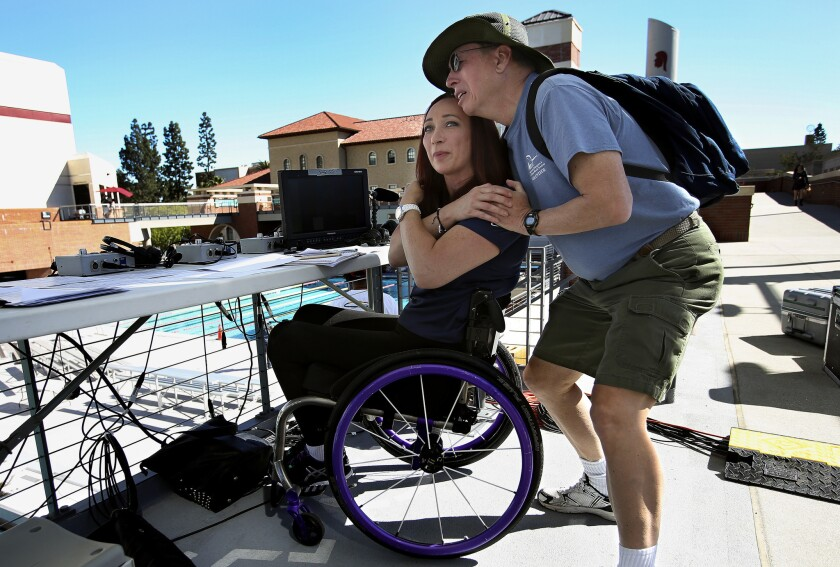 Six-time Olympic gold medalist Amy Van Dyken has kept a positive outlook after suffering a severed spinal cord last June and is an inspiring figure to admirers such as John Lewis, above, who met her at a recent event at USC and became emotional.