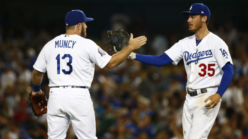 Dodgers first baseman Max Muncy (13) and first baseman Cody Bellinger (35) congratulate each other after defeating the Angels at Dodger Stadium on Friday.
