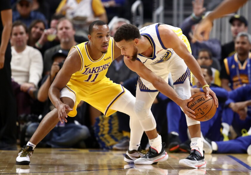 Lakers guard Avery Bradley plays tight defense on Warriors guard Stephen Curry on Oct. 5, 2019.