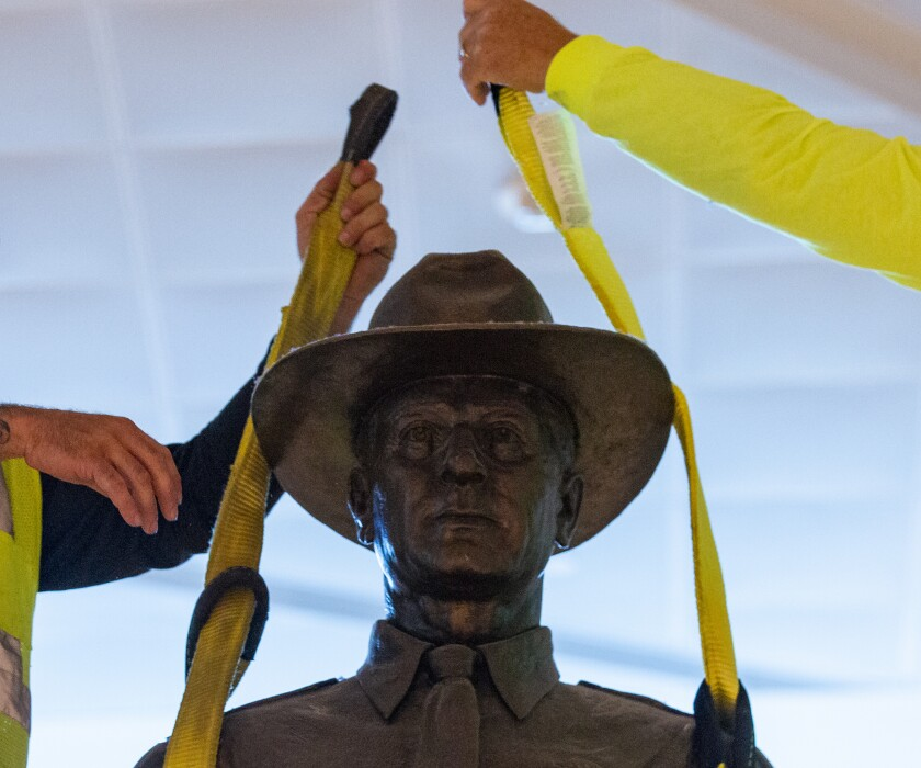 """A Phoenix 1 Restoration & Construction crew removes a 12-foot-tall bronze statue of a Texas Ranger, called """"One Riot, One Ranger,"""" from the main lobby inside Love Field airport on Thursday, June 4, 2020 in Dallas. A published account of brutal and racist chapters in the history of an elite Texas investigative agency prompted Dallas officials to remove the statue from Love Field's passenger terminal that honored the agency. (Juan Figueroa/ The Dallas Morning News via AP)"""