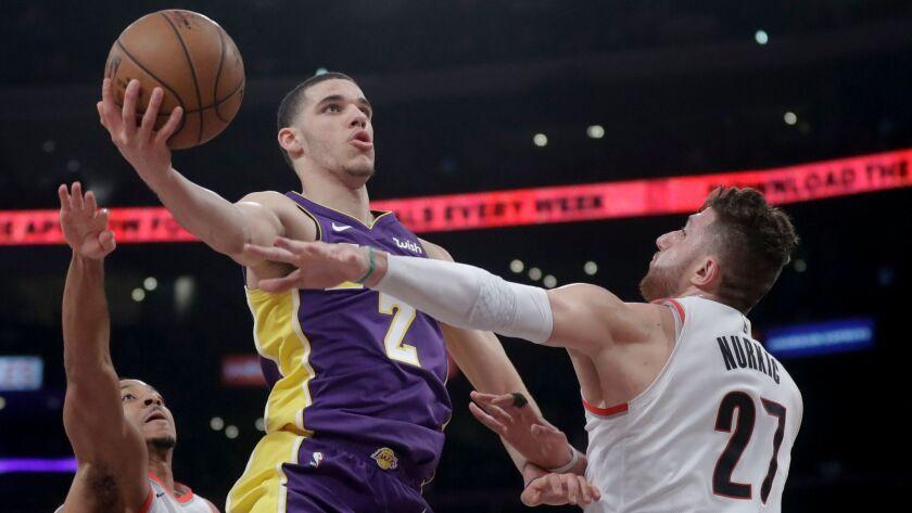 Los Angeles Lakers guard Lonzo Ball shoots between Portland Trail Blazers guard CJ McCollum, left, a