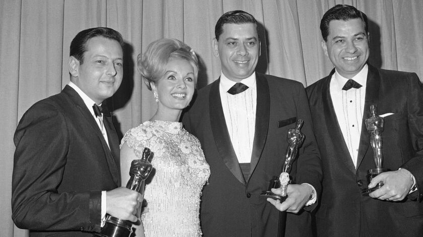 André Previn, from left, receiving his fourth Academy Award in 1965 with Debbie Reynolds, Bob Sherman and Dick Sherman.