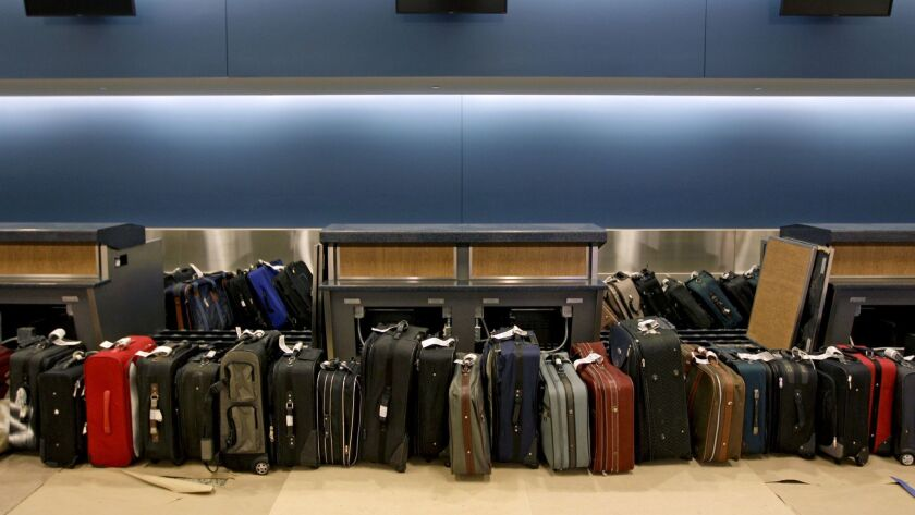 FILE - In this March 28, 2012, file photo, luggage waits to be run through the baggage system for te