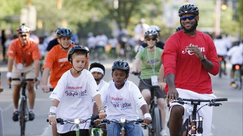 LeBron James, right, finishes his ride during the LeBron James Family Foundation, King for Kids Bike-a-thon, in Akron, Ohio, on Aug. 7, 2010.