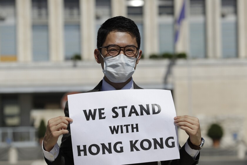 FILE - In this Aug. 25, 2020, file photo, Hong Kong activist Nathan Law takes part in a protest during a meeting of Chinese Foreign Minister Wang Yi with Italian Foreign Minister Luigi Di Maio, in Rome. Hong Kong democracy activists have launched a new push to continue their fight among residents living abroad in the wake of a sweeping crackdown by Beijing and changes to the the semi-autonomous Chinese city's electoral system aimed at shutting out opposition voices. (AP Photo/Andrew Medichini, file)