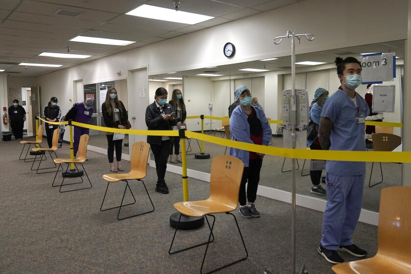 """FILE - In this Dec. 24, 2020, file photo, healthcare workers wait in line to receive the Pfizer-BioNTech COVID-19 vaccine at Seton Medical Center in Daly City, Calif. San Diego County is opening what it calls a """"vaccination super station"""" that aims to inject up to 5,000 health care workers daily with a COVID-19 vaccine, officials said Friday, Jan. 8, 2021. The effort that begins Monday, Jan. 11, is one of the most ambitious yet in California to accelerate the pace of vaccinations that Gov. Gavin Newsom said this week was """"not good enough."""" (AP Photo/Jeff Chiu, File)"""