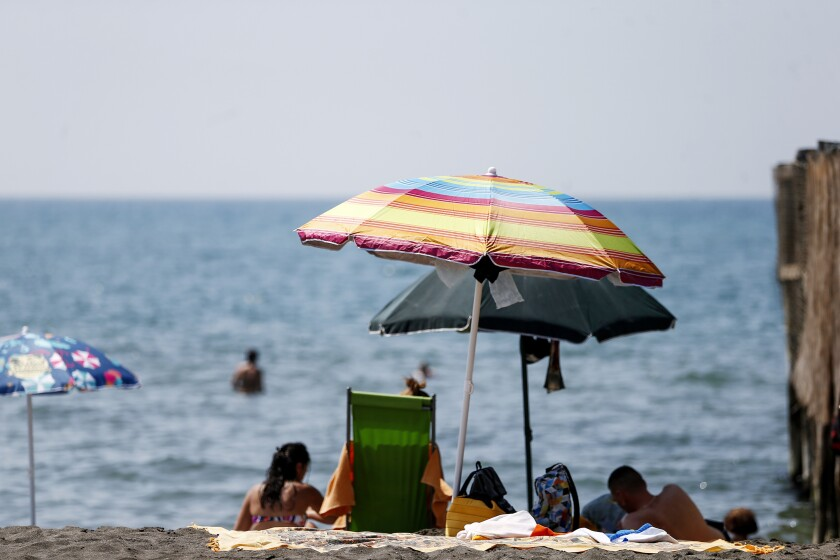 People enjoy a day at the beach, in Ostia, in the outskirts of Rome, Saturday, Aug. 14, 2021. A heat wave settled over southern Europe threatened temperatures topping 45 degrees Celsius (113 degrees Fahrenheit) in many parts of the Iberian Peninsula on Saturday while Italian authorities expanded to 16 the number of cities on red alert for conditions that can pose a health risk to the elderly and vulnerable. (Cecilia Fabiano/LaPresse via AP)