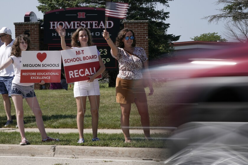 Supporters to recall the entire Mequon-Thiensville School District board wave at cars outside Homestead High School Monday, Aug. 23, 2021, in Mequon, Wis. A loose network of conservative groups with ties to major Republican donors and party-aligned think tanks is quietly lending firepower to local activists engaged in the culture war fights in schools across the country. (AP Photo/Morry Gash)