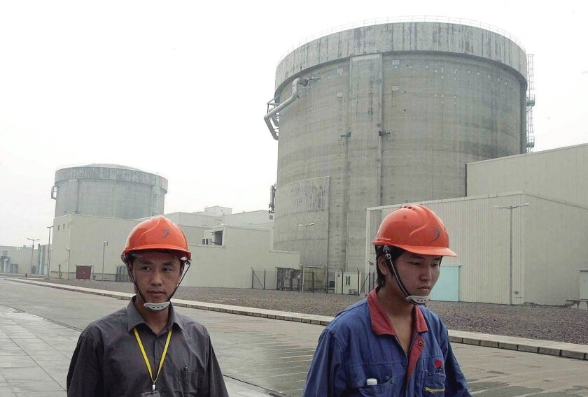 FILE - In this June 10, 2005 file photo, workers walk past a part of the Qinshan No. 2 Nuclear Power Plant, China's first self-designed and self-built national commercial nuclear power plant in Qinshan, about 125 kilometers (about 90 miles) southwest of Shanghai, China. Beijing's wants to compete w