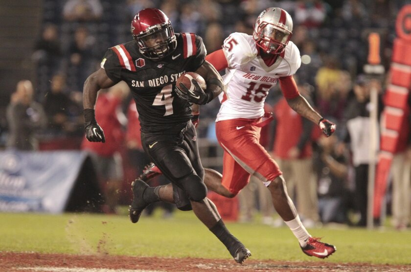 The  Aztecs' Adam Muema carries the ball while chased by New Mexico's SaQuwan Edwards in the 4th quarter.