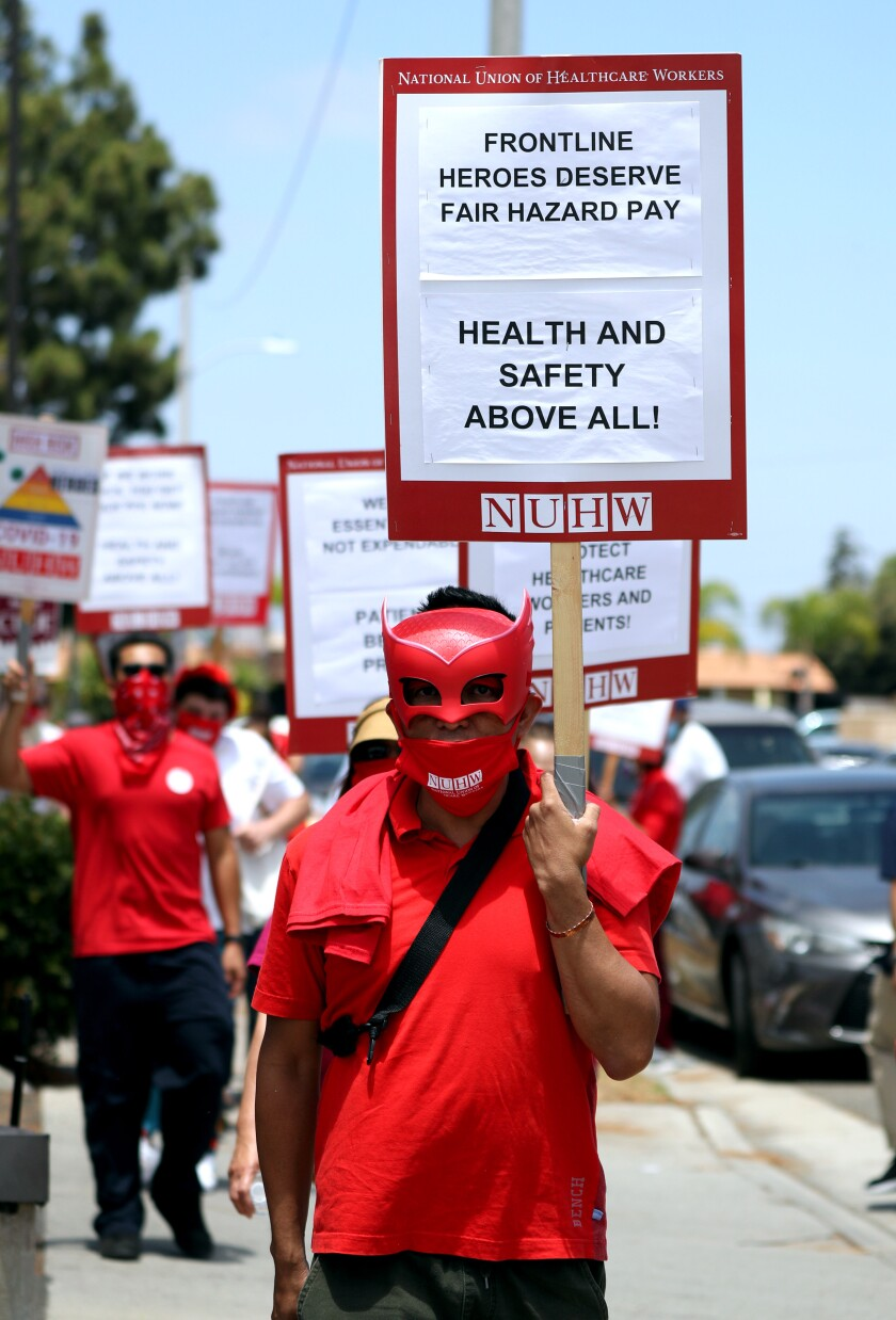 A protester at Kindred Hospital in Westminster wears a mask and a sign demanding fair hazard pay for frontline workers.