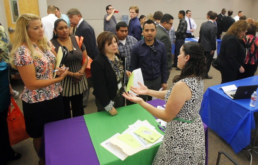 Gema Medina (left) collects information from Kasey Cheal of Love Right Home Care of San Diego on April 19 at a job fair sponsored by North County Career Centers in Carlsbad, California.
