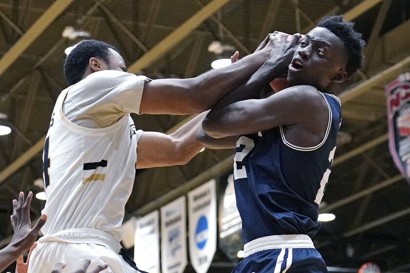 Mount St. Mary's forward Nana Opoku, right, and Bryant forward Hall Elisias compete for a rebound during the second half of an NCAA college basketball game for the Northeast Conference men's tournament championship Tuesday, March 9, 2021, in Smithfield, R.I. (AP Photo/Charles Krupa)