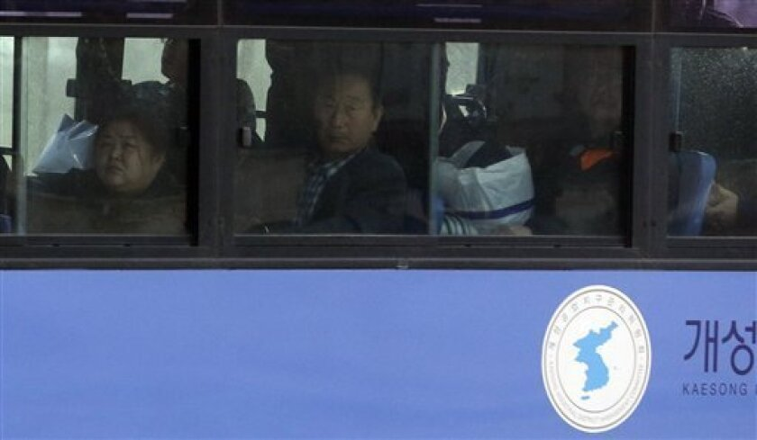 South Koreans look out a bus window upon their arrival from North Korea's Kaesong at the customs, immigration and quarantine office near the border village of Panmunjom, which has separated the two Koreas since the Korean War, in Paju, north of Seoul, South Korea, Tuesday, April 9, 2013. A few hund