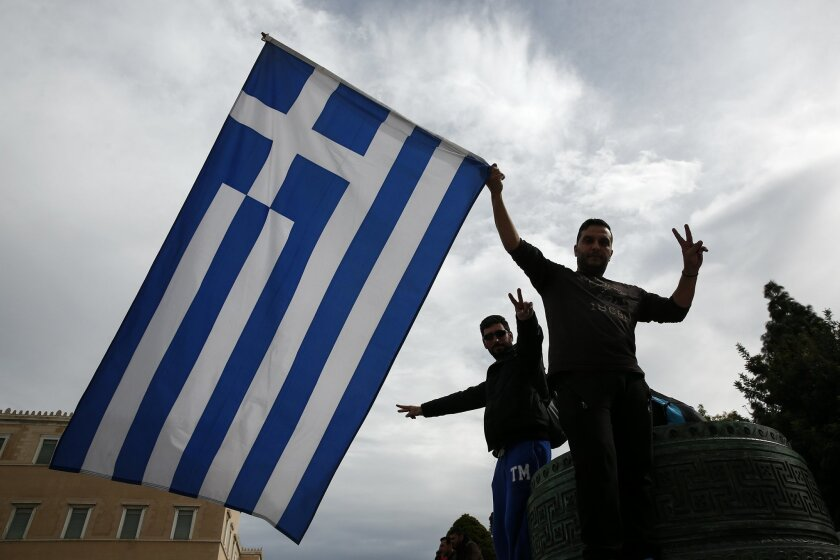 Farmers wave a Greek flag during an anti-government rally in front of the parliament in Athens, on Saturday, Feb. 13, 2016. Farmers from across Greece gather in Athens for a two-day protest against the government and its plans to impose new tax hikes and pension charges. Bailout lenders are demandi