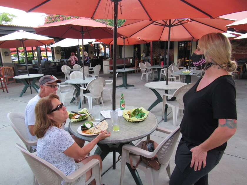 Melanie Brookes speaks with Karen and Ross Ellis at a patio table at the Downtown Cafe in El Cajon last year.