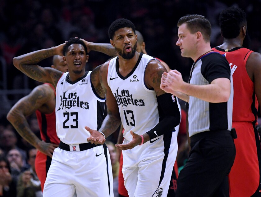 Clippers forward Paul George (13) and guard Lou Williams (23) react to a foul call during a loss to the Rockets on Dec. 19, 2019, at Staples Center.