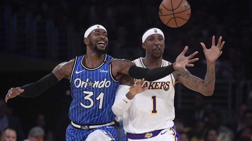 Orlando Magic guard Terrence Ross, left, and Lakers guard Kentavious Caldwell-Pope reach for a loose ball during the first half on Sunday.