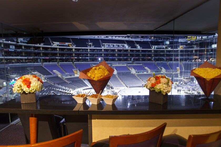 Flower bouquets and munchies in cones are ready for spectatorss inside a luxury suite at Staples Center.