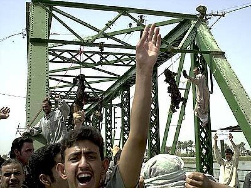 A crowd gathers as charred bodies hang from a bridge over the Euphrates River in Fallujah, west of Baghdad. Enraged Iraqis in this hotbed of anti-Americanism killed four foreigners Wednesday, including at least one U.S. national, took the charred bodies from a burning SUV, dragged them through the streets, and hung them from the bridge.