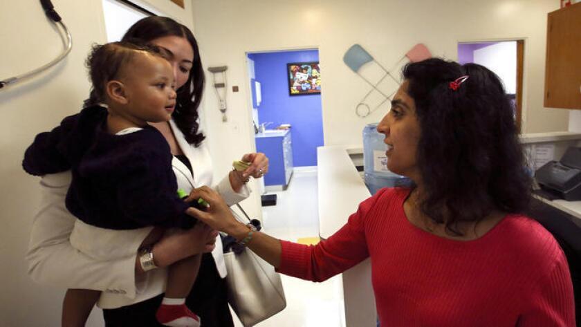 Monica Asnani, a la derecha, le dice adios a Kristian Richard, de1 año, mientras es sostenido por su mamá, Natasha, despues de que el niño recibio la vacuna del sarampion, paperas y rubeola en Medical Arts Pediatric Med Group en Wilshire Boulevard en Los Angeles.