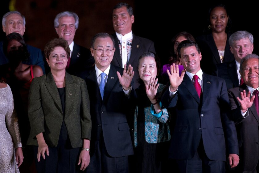 Heads of state, some with their spouses, gather for an informal group photo prior to a gala dinner after the opening ceremony of the Summit of the Americas in Panama City, Panama, Friday, April 10, 2015. From left, front row, is Brazil's President Dilma Rousseff, United Nations Secretary General Ban Ki-Moon and his wife Mrs. Ban Soon-taek, Mexico's President Enrique Pena Nieto and El Salvador's President Salvador Sanchez Ceren. From left, top row, is an unidentified man, Uruguay's President Tabare Vazquez, Ecuador's President Rafael Correa, an unidentified woman and Canada's Prime Minister Stephen Harper. (AP Photo/Dario Lopez-Mills)