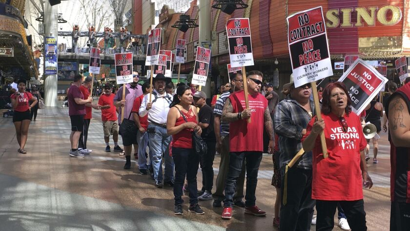 Housekeepers, bartenders and other unionized workers picket Friday outside a Las Vegas casino-hotel in their latest push for a new contract.