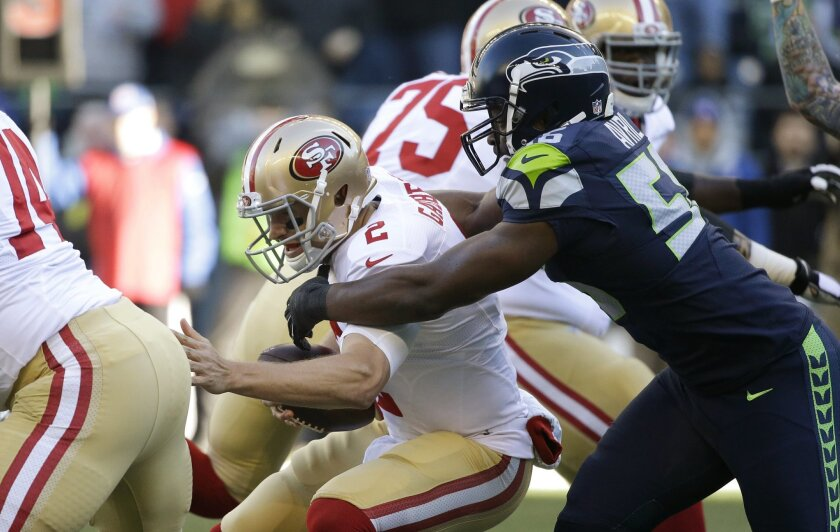 FILE - In this Nov. 22, 2015 file photo, Seattle Seahawks defensive end Cliff Avril, right, sacks San Francisco 49ers quarterback Blaine Gabbert during the first half of an NFL football game, in Seattle. The 49ers will play against the Arizona Cardinals on Sunday, Nov. 29, 2015, with Gabbert under center. (AP Photo/Elaine Thompson, File)