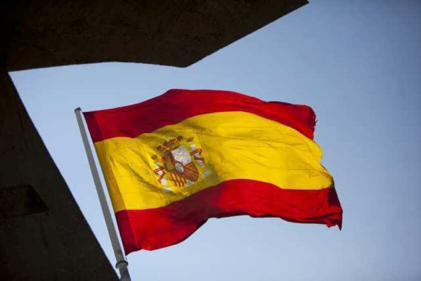 A Spanish national flag flies in Madrid. Spain is poised to become the fourth of the 17 euro-area countries to require emergency assistance as the currency bloc's finance chiefs plan weekend talks on a potential aid request to shore up the nation's lenders.