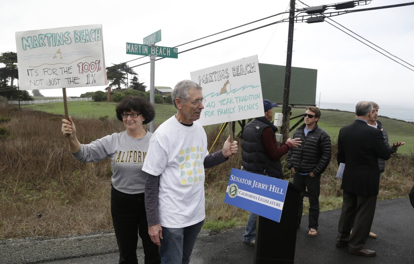 Protesters hold up signs in support of a beach access bill near Martin's Beach in Half Moon Bay, Calif.