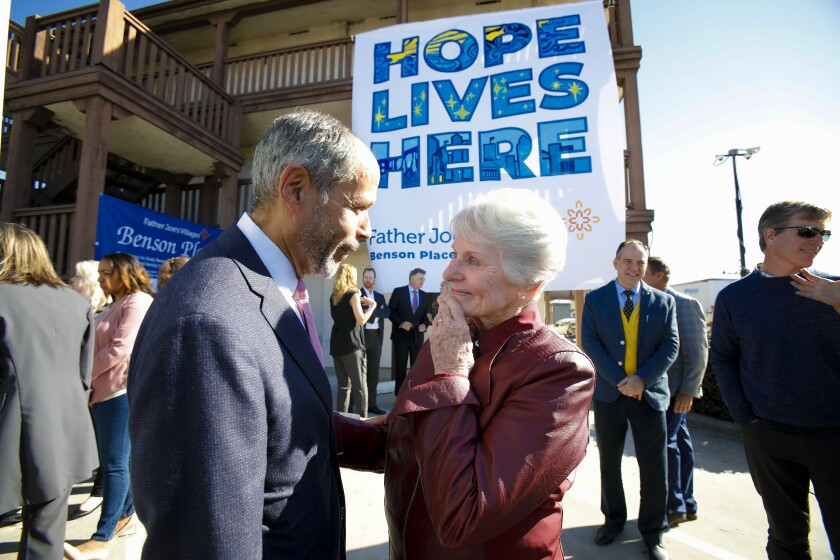 Deacon Jim Vargas speaks with Judy Benson after she became emotional during the unveiling of a banner Tuesday at the Benson Place, a project she helped fund that will house and provide support services for 82 formerly homeless people. The old motel at the site will be converted and open as Benson Place by the end of the year.