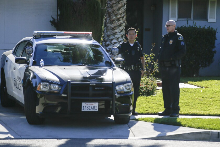 Several Anaheim police officers keep watch over the neighborhood while crime scene investigators collect evidence left behind by protesters at the home of an LAPD officer in Anaheim.