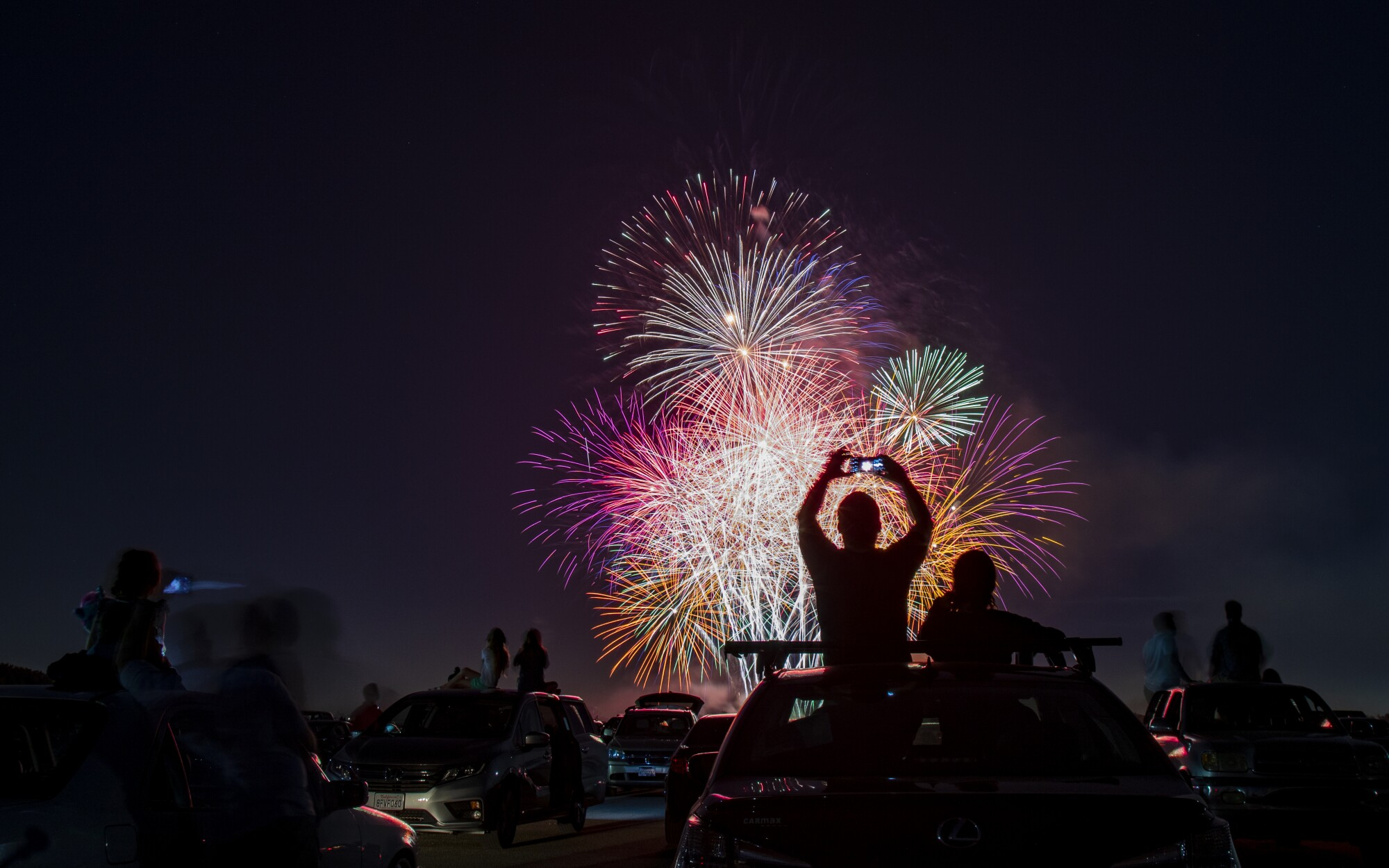Spectators sit on the roofs of their vehicles to watch the fireworks during the Drive-Up 4th of July Spectacular