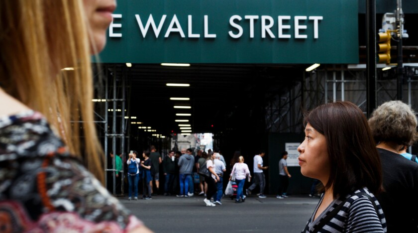 People walk past a sign for a building on Wall Street near the New York Stock Exchange.