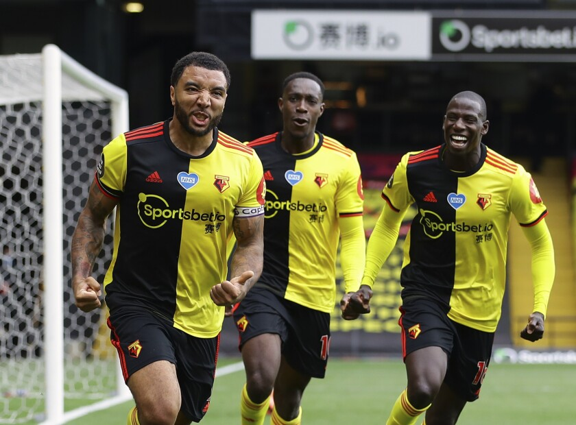 Watford's Troy Deeney, left, celebrates with teammates after scores his side's second goal from the penalty spot during the English Premier League soccer match between Watford and Newcastle at the Vicarage Road Stadium in Watford, England, Saturday, July 11, 2020. (Richard Heathcote/Pool via AP)