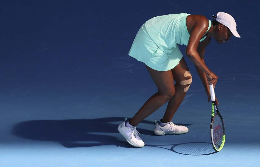 United States' Venus Williams reacts as she injures her leg during her second round match against Italy's Sara Errani at the Australian Open tennis championship in Melbourne, Australia, Wednesday, Feb. 10, 2021.(AP Photo/Hamish Blair)